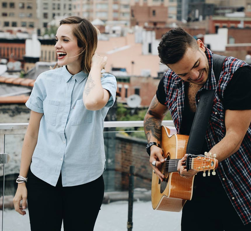 man and woman playing music on a city building rooftop