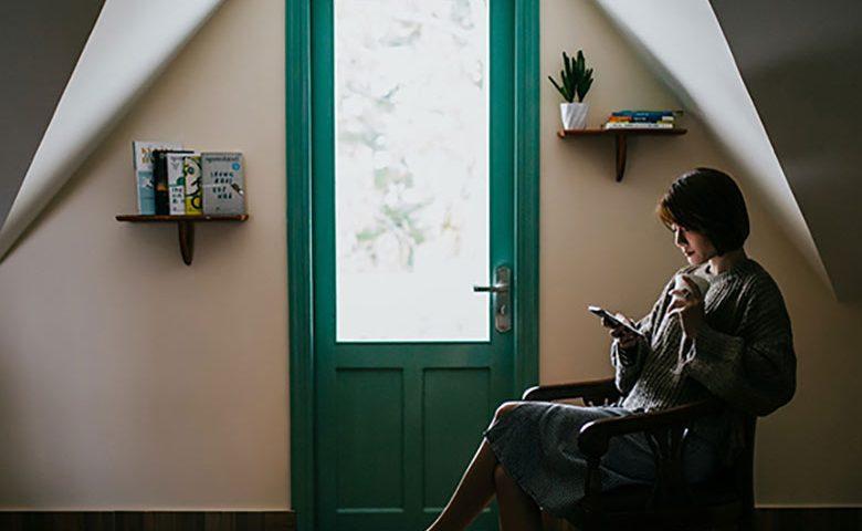 woman sitting indoors near door