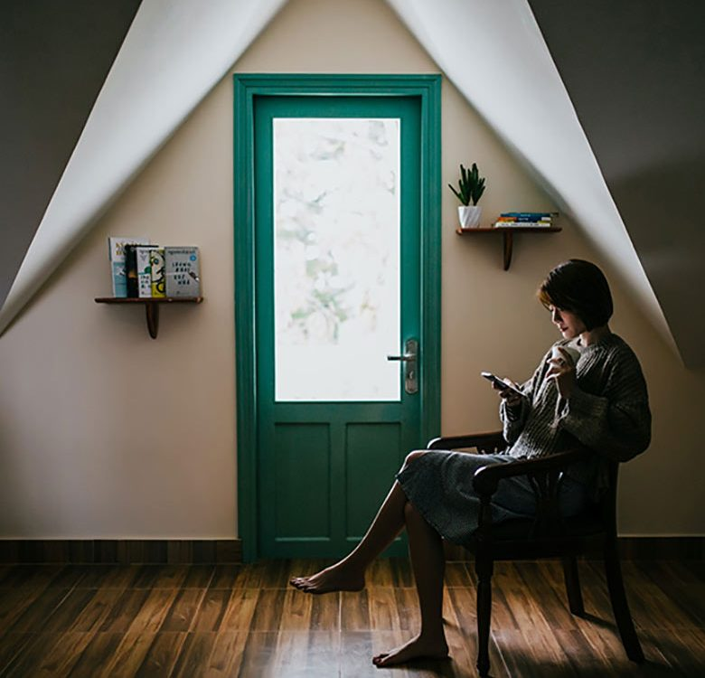 woman sitting indoors near door